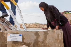 A woman from the Tuba community in the West Bank watches as water is poured into a cisten funded by ECHO. March 22nd, 2013. Credit: Wikipedia CC