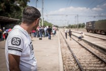 Maher from Damascus, travelled by boat to Europe, and then on foot to Macedonia where he waits for a train. Credit: Stephen Ryan / IFRC